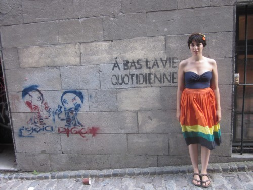 "julia posing next to a stencilled graffiti that reads ""à bas la vie quotidienne"""