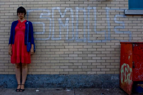 a photo of julia, a young femme presenting person, standing next to a silver graffiti that reads SMILE. she is not smiling.
