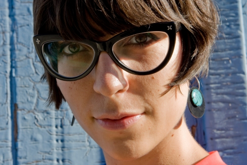 a close up portrait of julia wearing large cat eye glasses looking at the camera