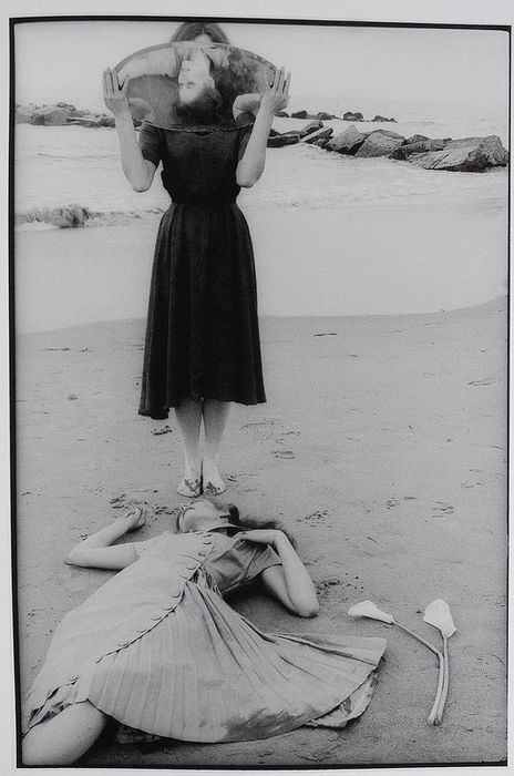 Photograph by Francesca Woodman holding up a mirror on a beach