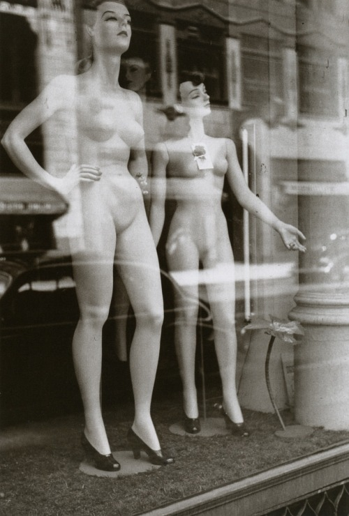 Two female mannequins stand undressed in a windowshop front in the 1940s. Photographed by John Vachon