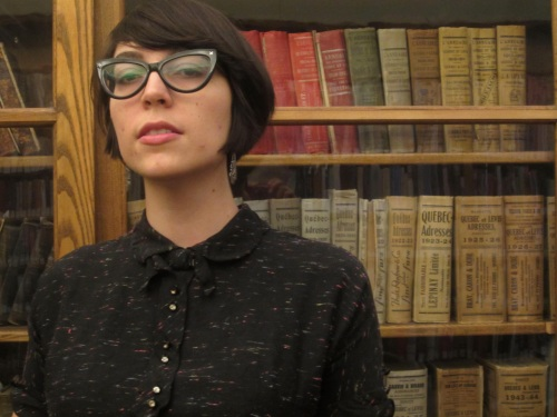Julia poses in front of old books in Quebec City's historic Morrin Centre