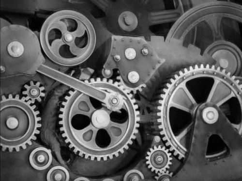 A film still from Charlie Chaplin's Modern Times (1936) showing Chaplin's character stuck in the gears of a giant machine