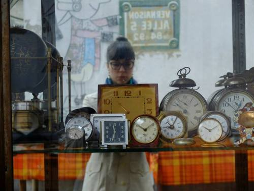 A self-portrait of the author taken in a mirror. A half-dozen old alarm clocks are in the foreground.