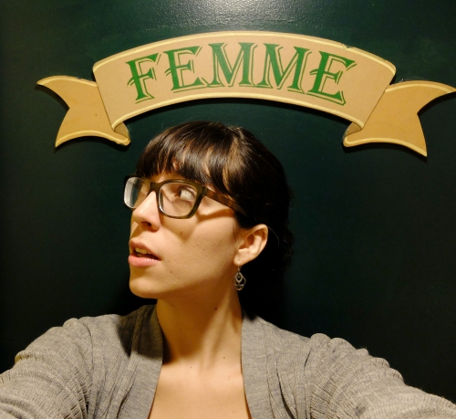A woman wearing glasses looks upwards. A banner painted on the wall reads FEMME, which means woman in French but also femme as in queer as in gay ;)